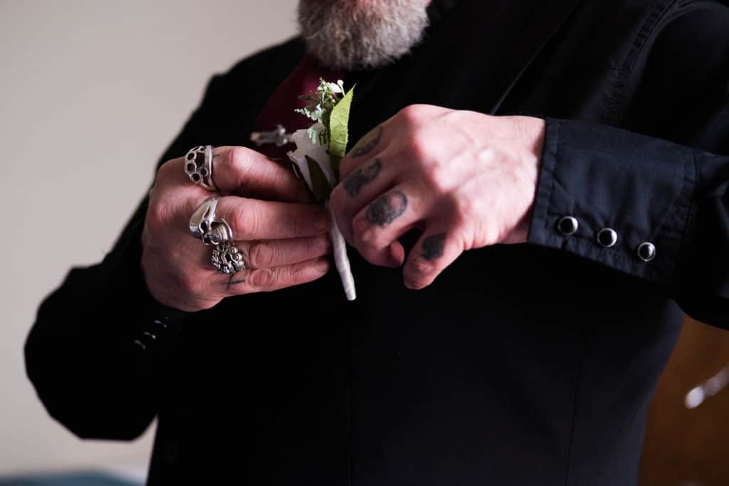 Groomsman portrait, close up of groomsman fixing his flowers